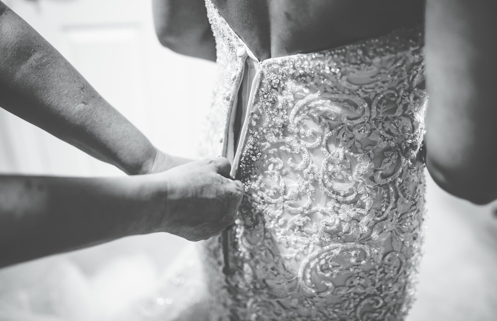 close up of bride's dress being fastened.