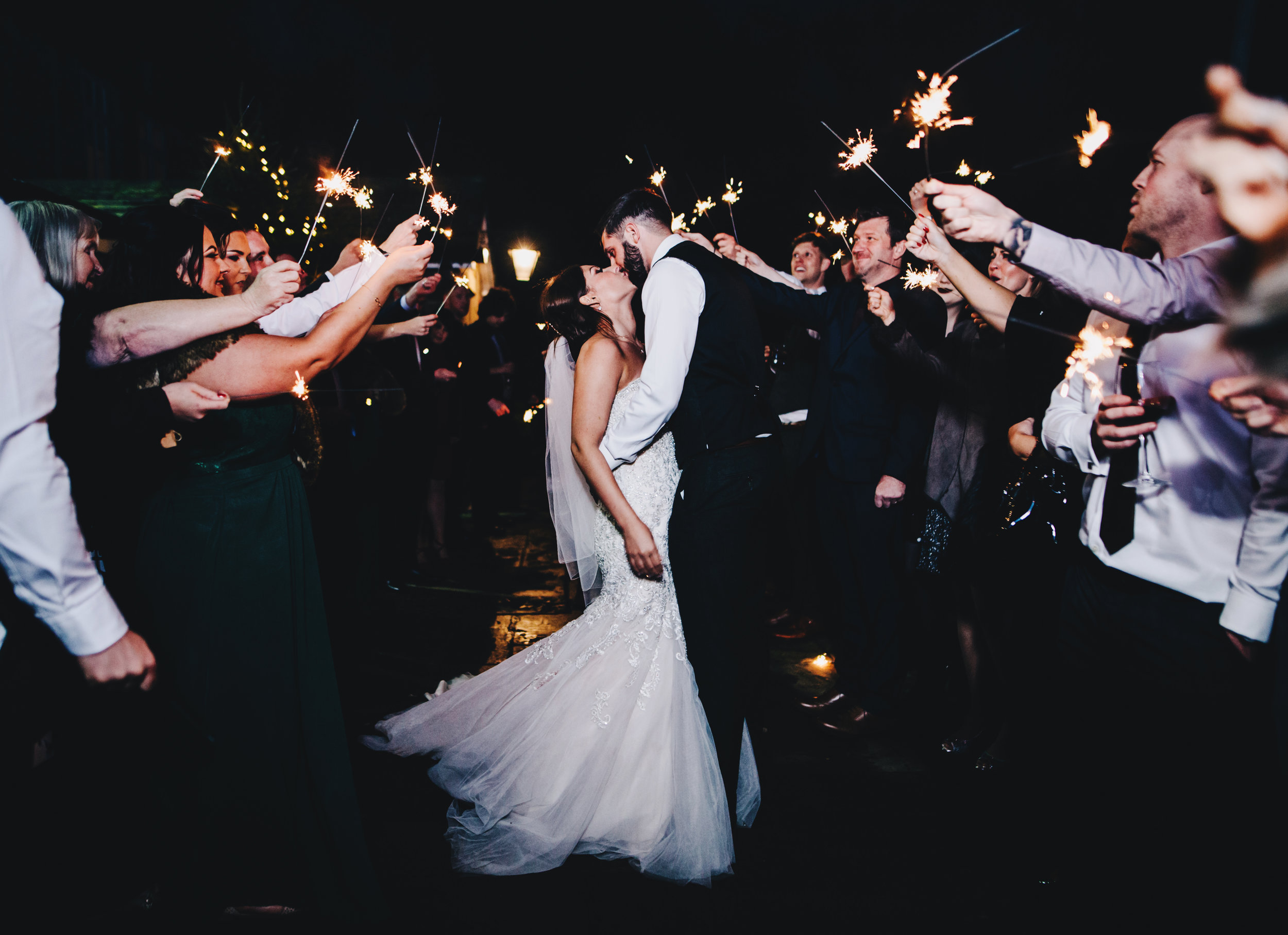 bride and groom kiss - sparklers at winter wedding