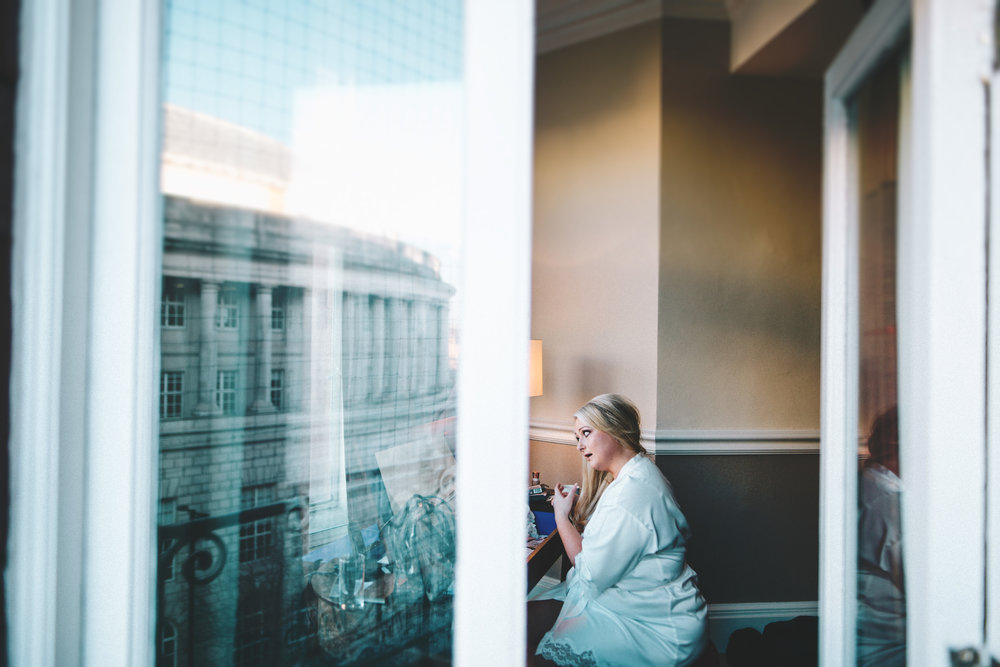 a layered images - bride putting on her make up. reflection of manchester library in the window