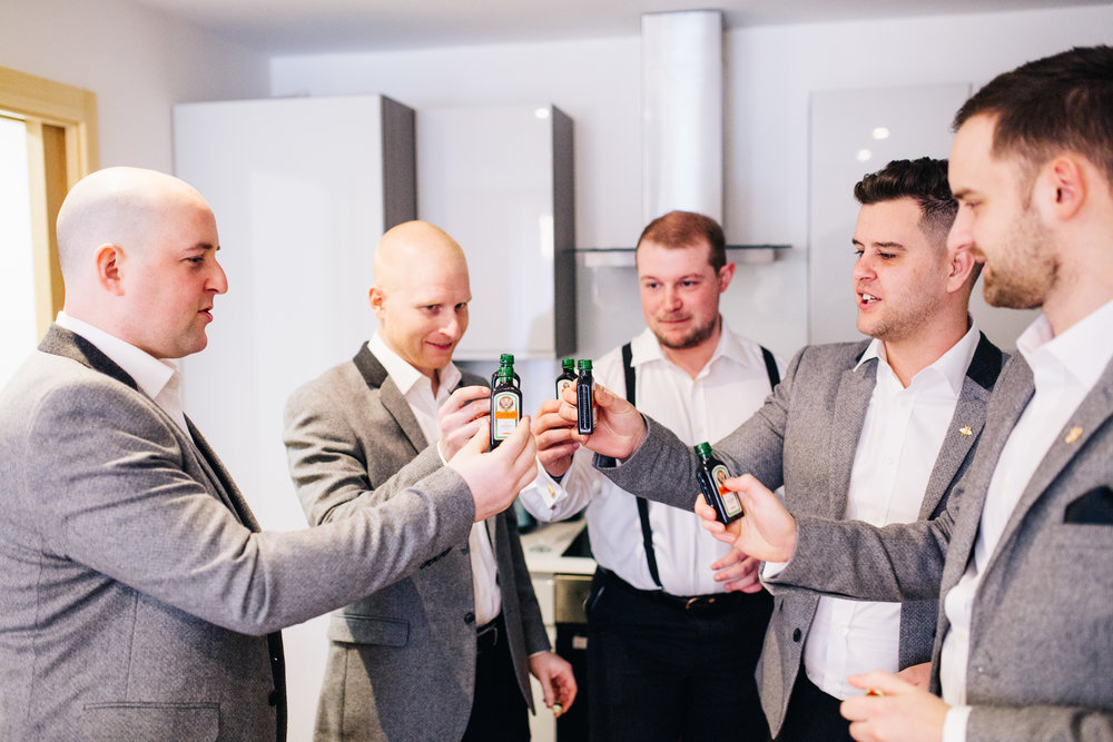 groomsmen share a drink before heading to manchester town hall for the wedding ceremony