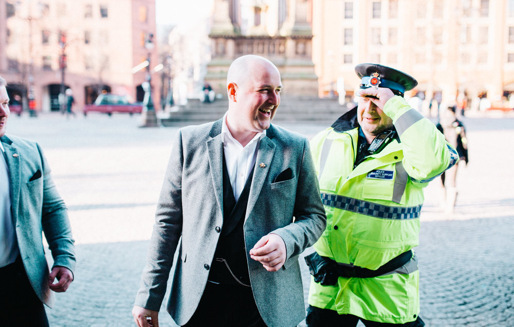 groom laughing with policeman outside manchester town hall