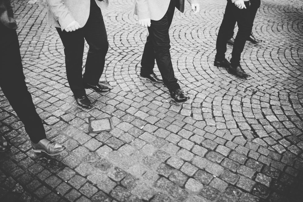 artistic wedding photography in manchester - groomsmen walking through town