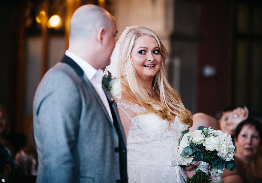 wedding images in manchester town hall - bride and groom smile to one another during the ceremony
