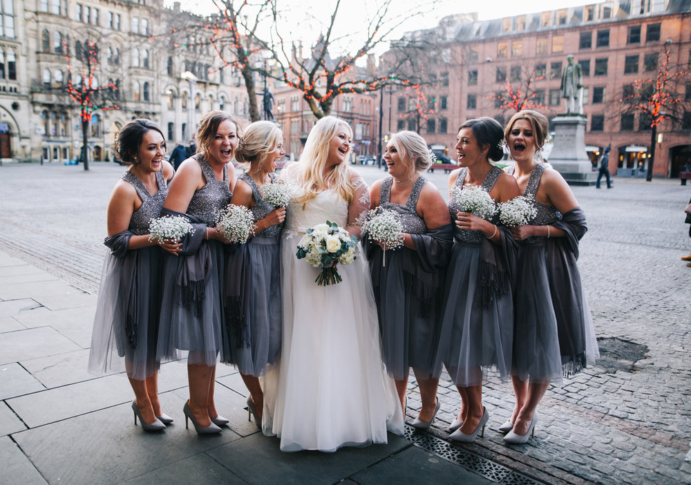 bride and her bridesmaids laughing with each other.