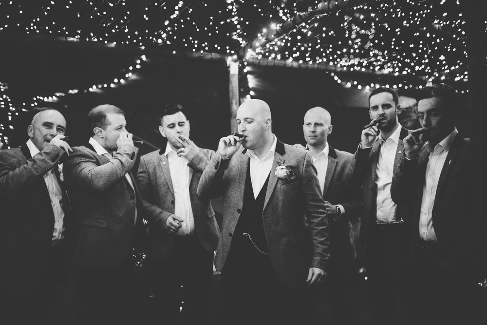 cool image of the grooms men sharing cigars