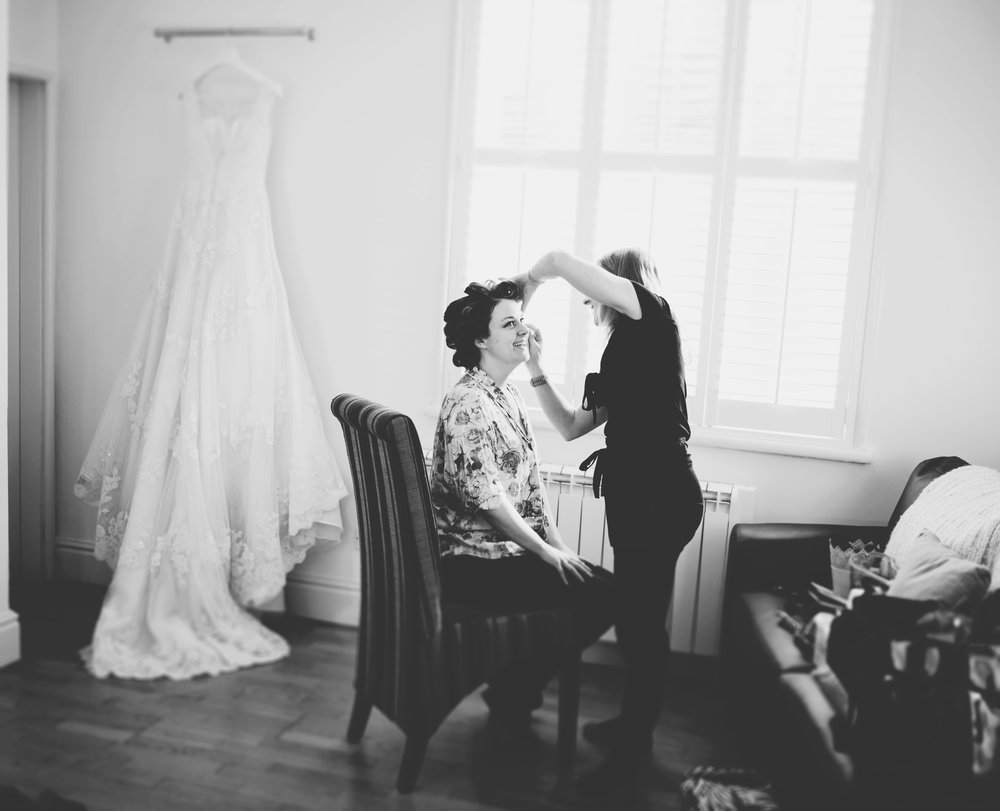 bride having her make up done on the morning of the wedding - dress in the background. Black and white wedding images