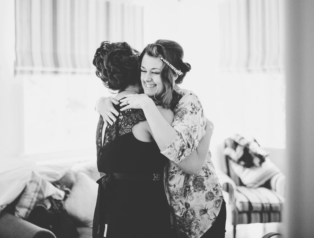 black and white wedding pictures -bride and bridesmaid embrace