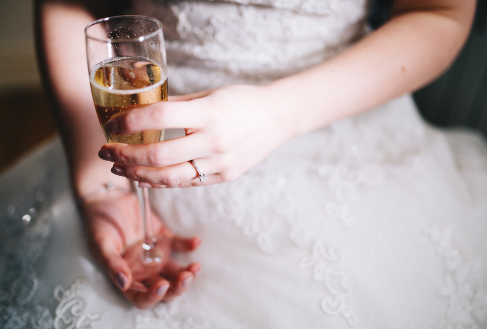 artistic wedding photographer - bride holding the champagne