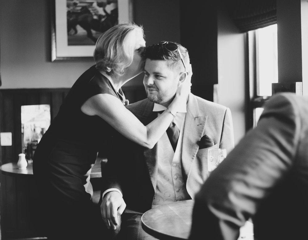 groom's mum kissing his head - documentary wedding photographer Lancashire