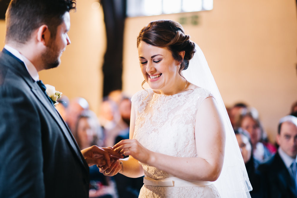 bride laughs as they exchange rings - samlesbury hall wedding photos.