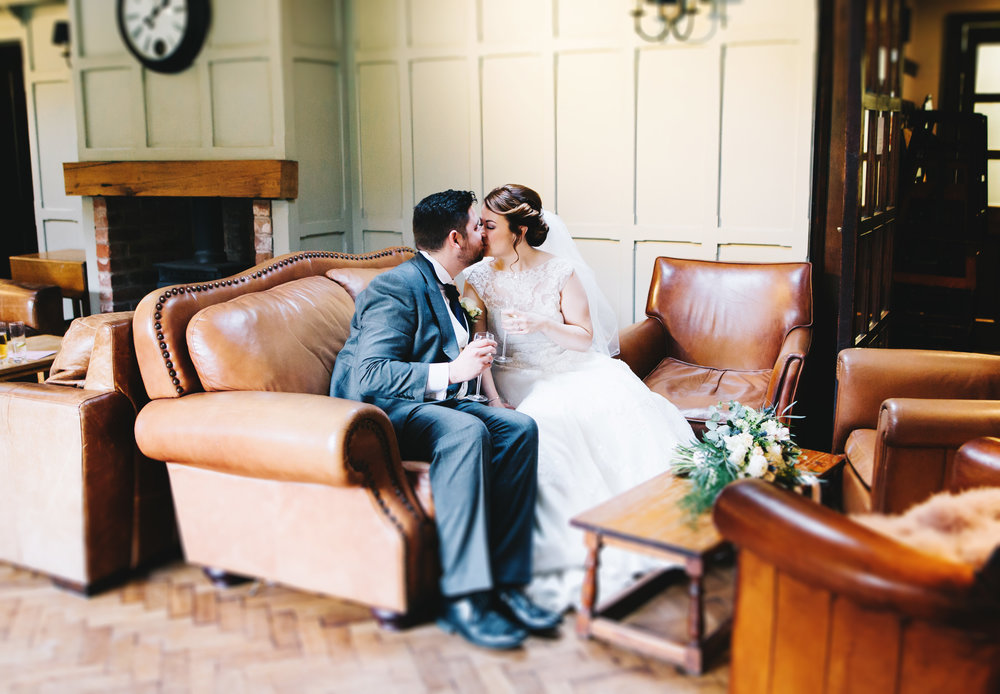 couple share a kiss in Samlesbury Hall just after the wedding ceremony