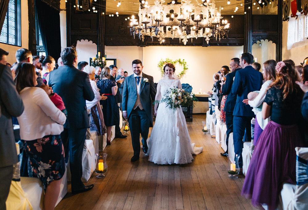 newlyweds walk down the aisle at samlesbury hall wedding