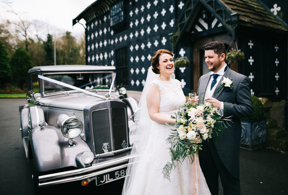 bride and groom laughing with each other outside samlesbury hall - wedding venues in Lancashire