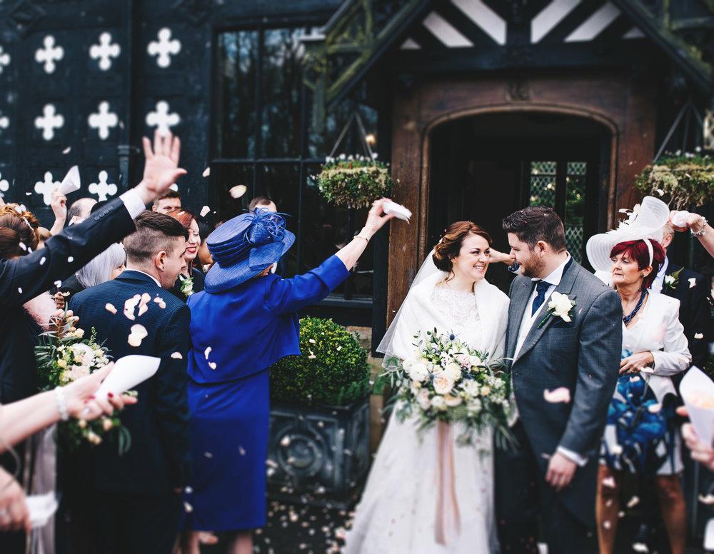 bride and groom laugh as they walk through confetti - lancashire wedding photographer