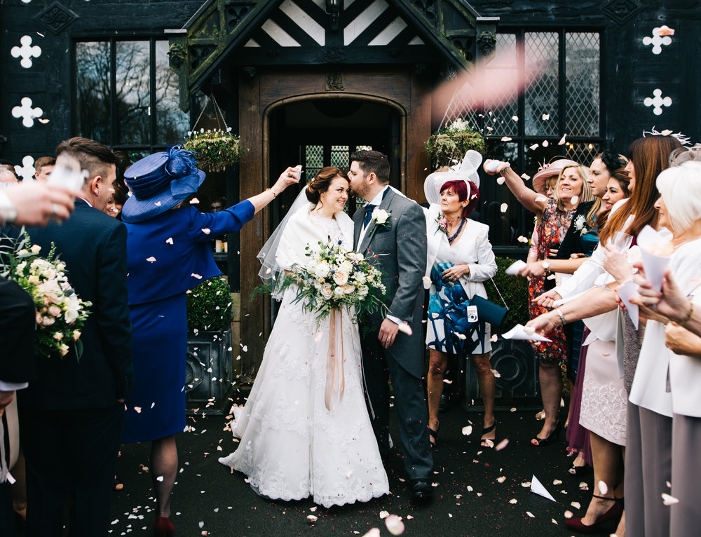guests throwing confetti outside samlesbury hall