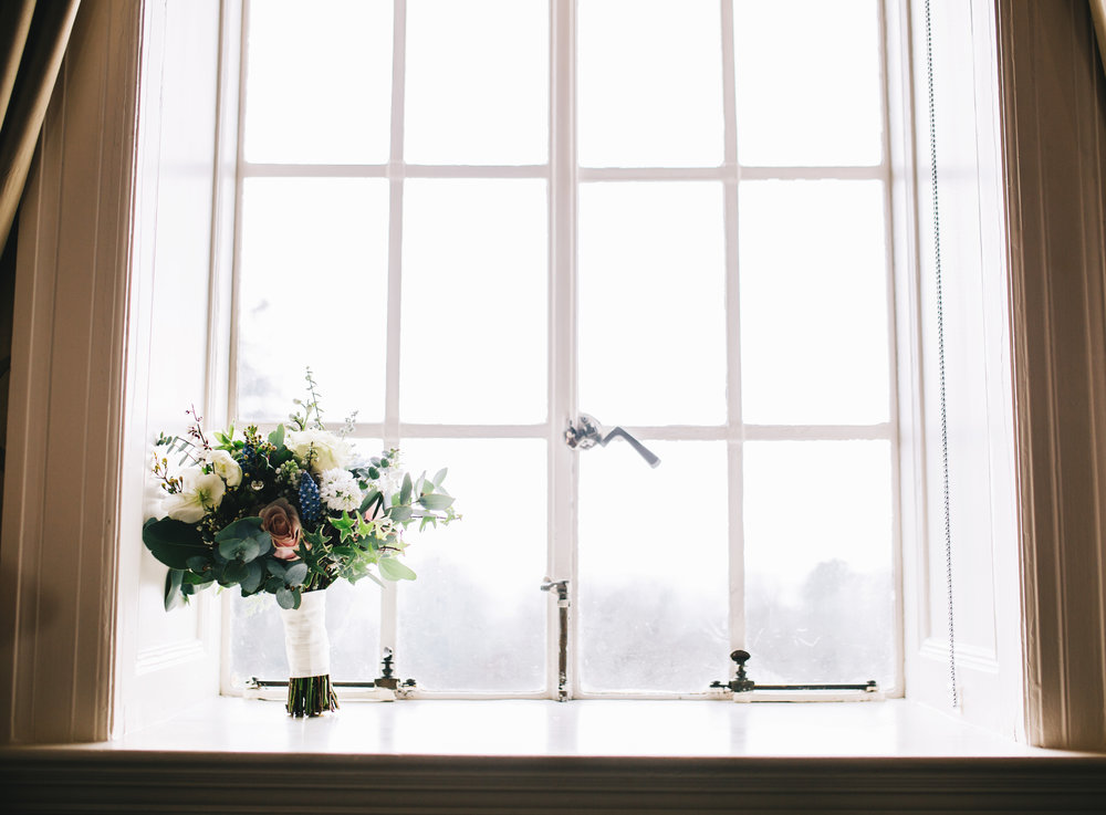 wedding flowers in the window of eaves hall