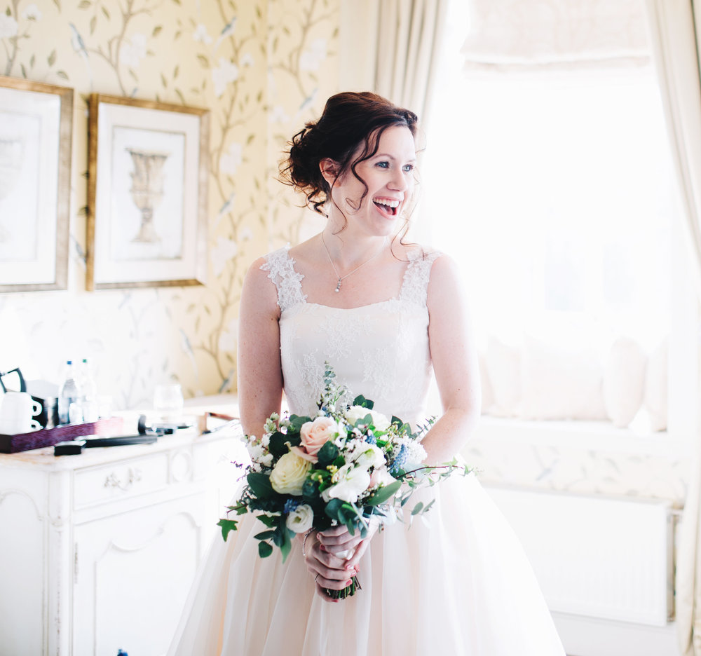 bride laughing in the bridal suite at eaves hall