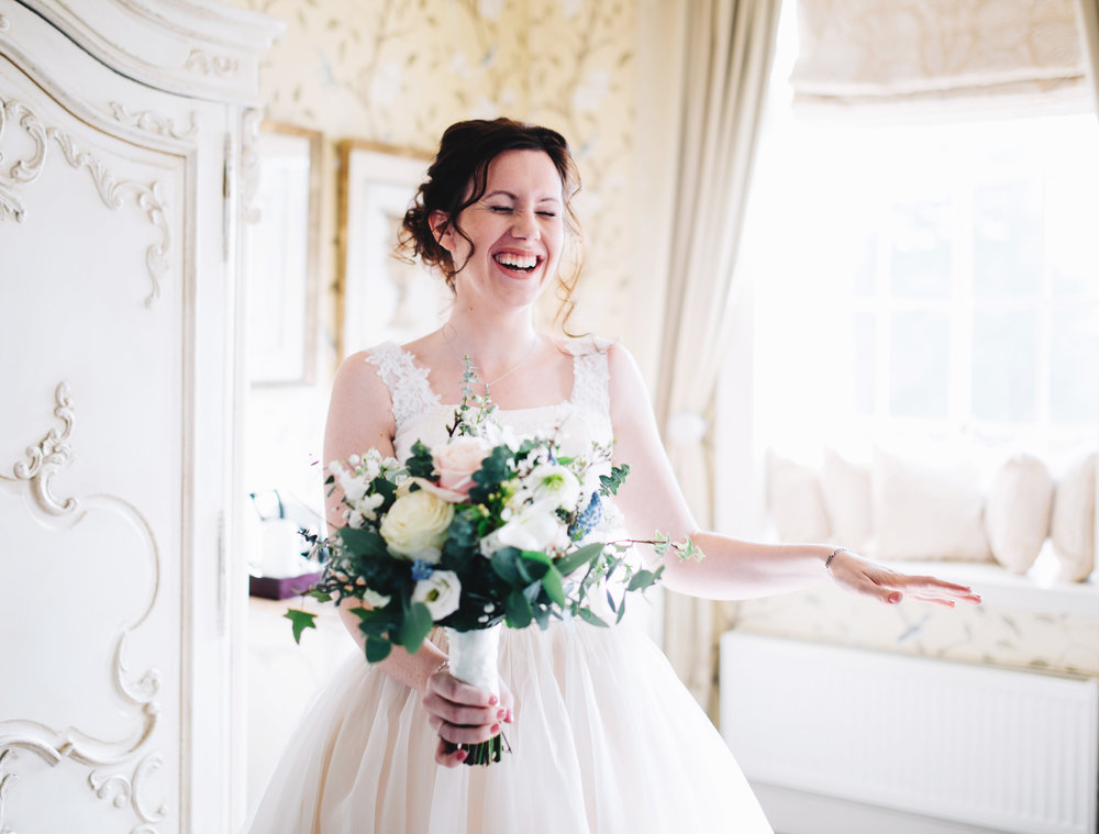 natural and documentary shot of bride laughing before her wedding ceremony