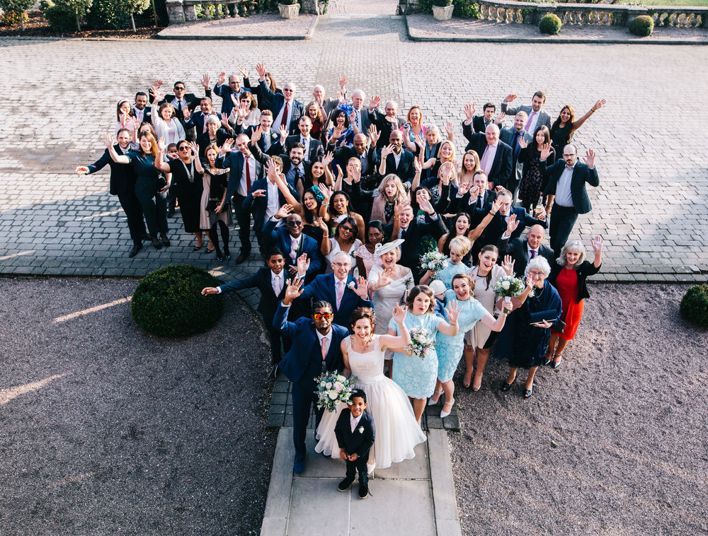 photograph of whole wedding party outside EAves Hall