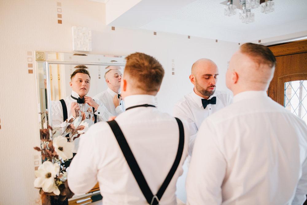 groom putting on his bowtie - black tie wedding in lancashire