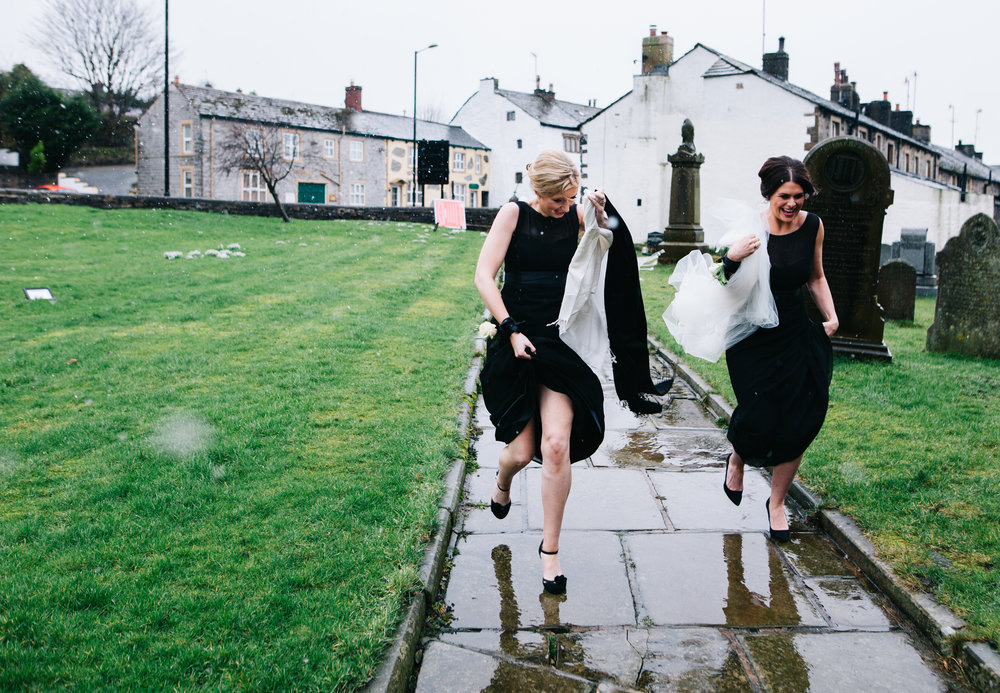 bridesmaids run through the rain to get into church