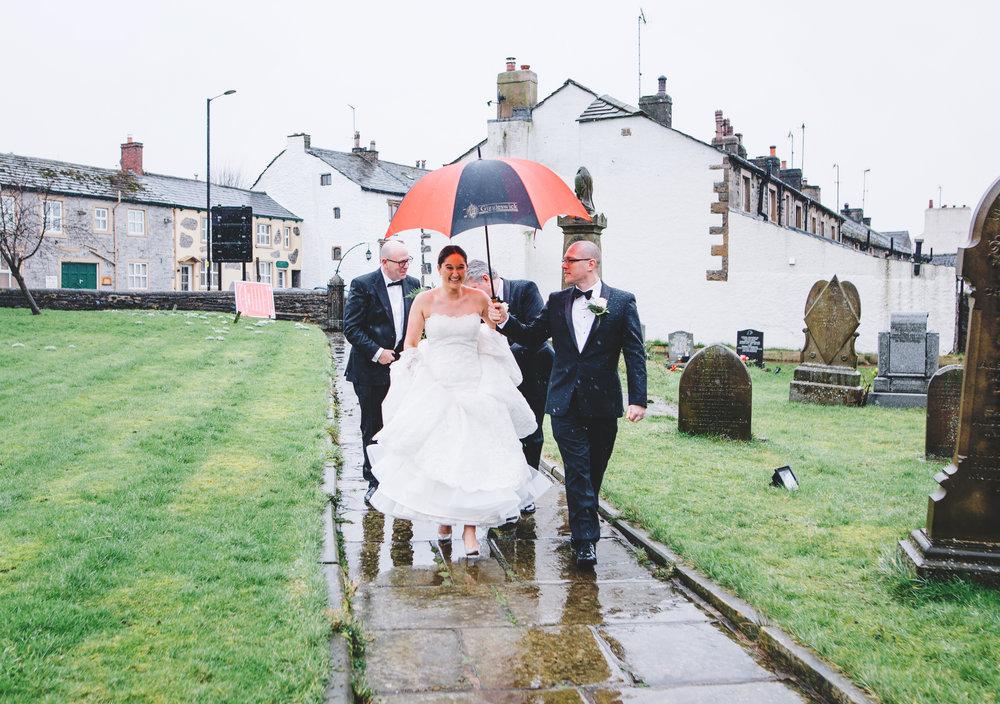 bride walks under an umbrella - winter wedding photography in lancashire