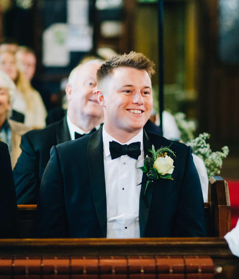 groom laughs as he waits for the bride to arrive