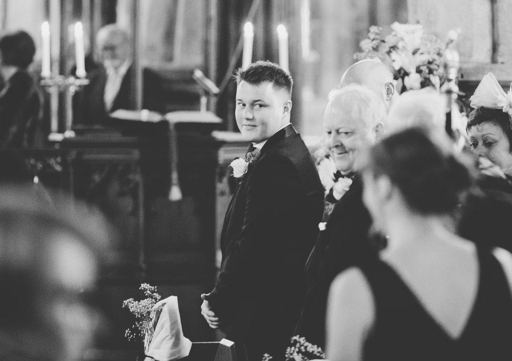 groom watches his bride arrive