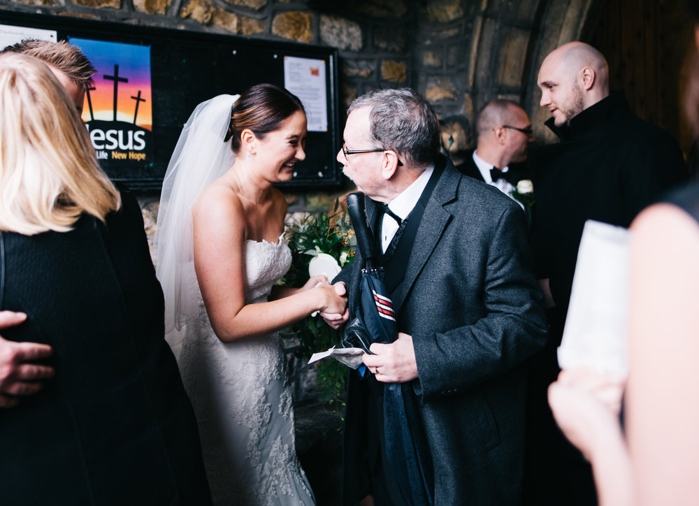bride greets guests outside lancashire wedding ceremony