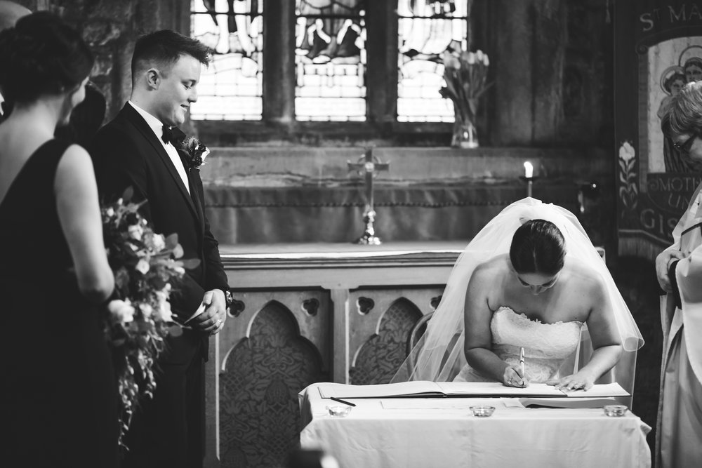documentary wedding picture of bride signing the register