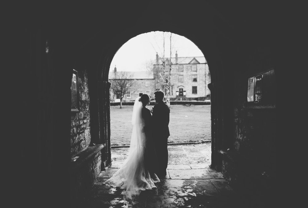 artistic black and white image of bride and groom in the church