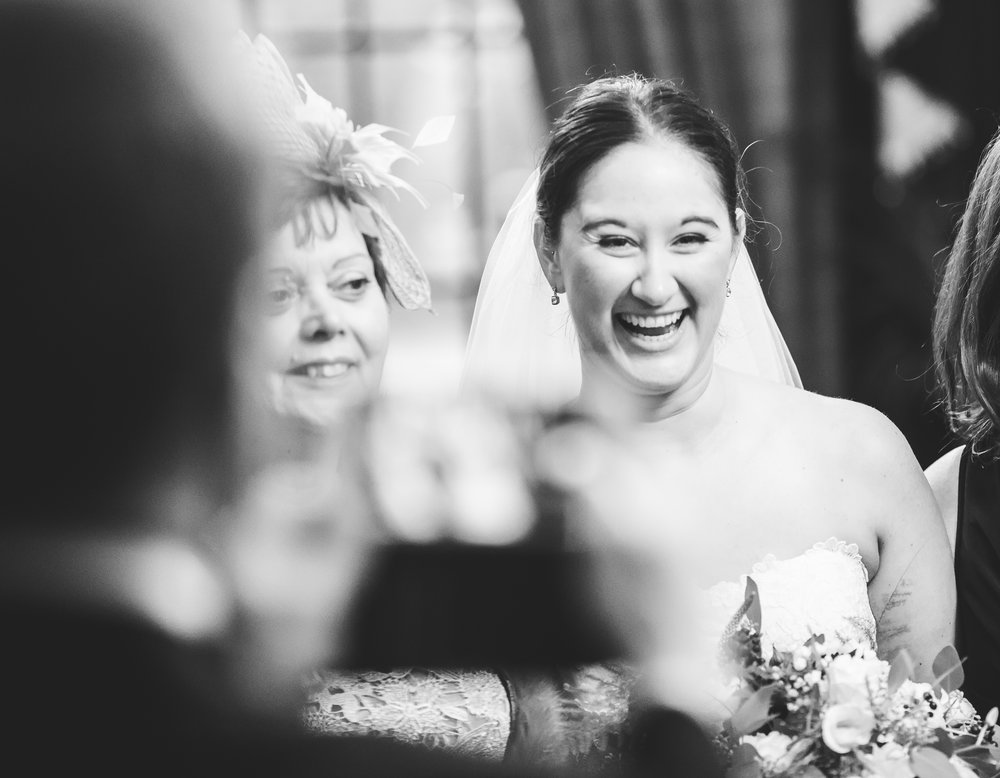 documentary images from eaves hall wedding - bride laughing with guests