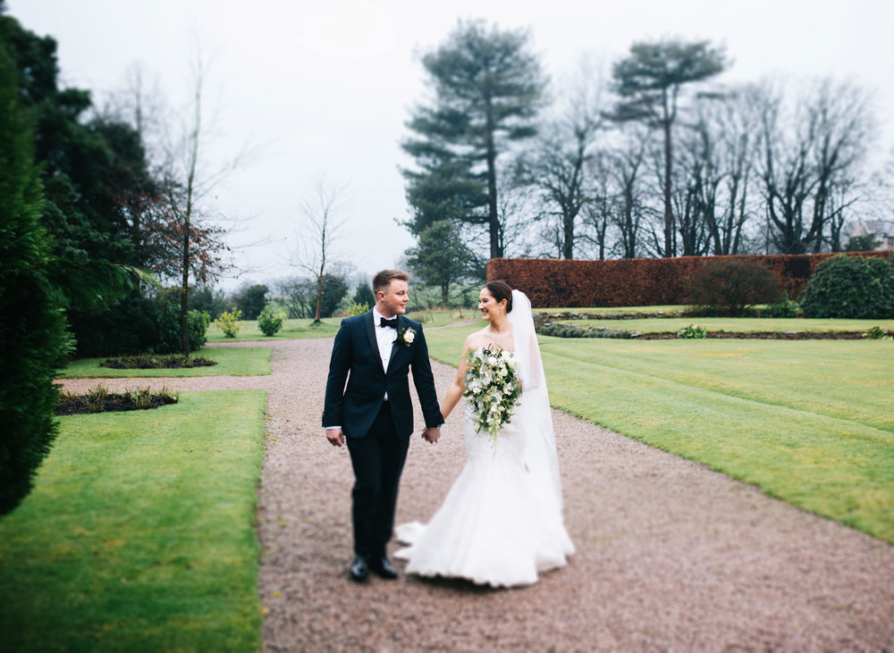 couple walk in the grounds at lancashire wedding venue eaves hall