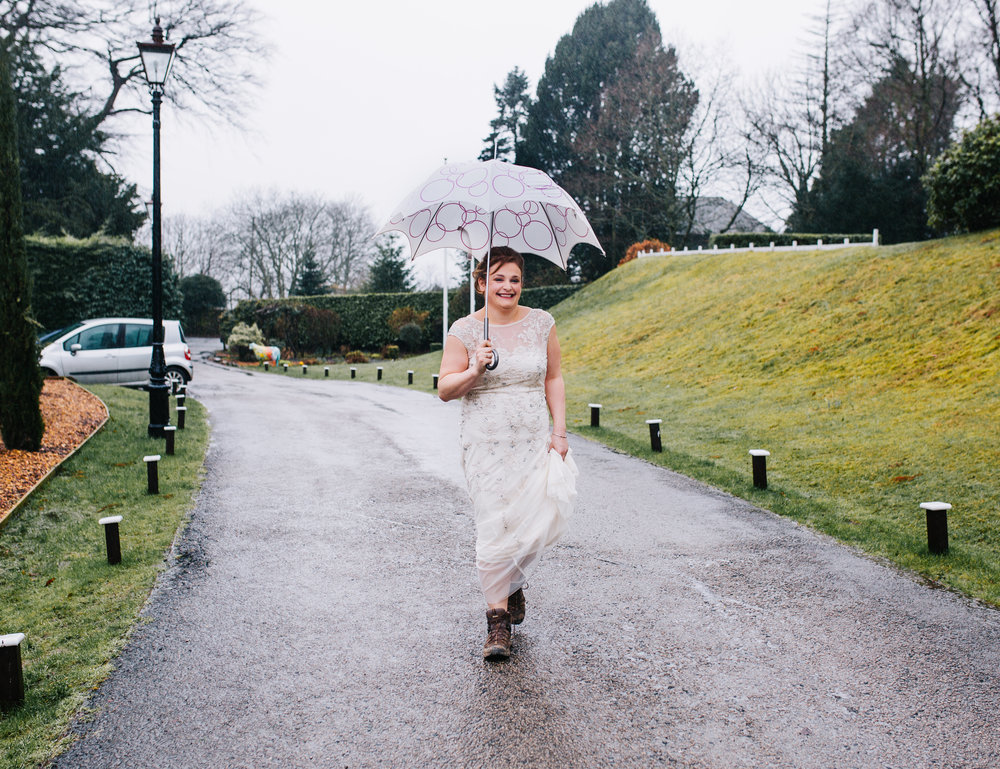 bride walks up to Broadoaks Country House hotel in the rain