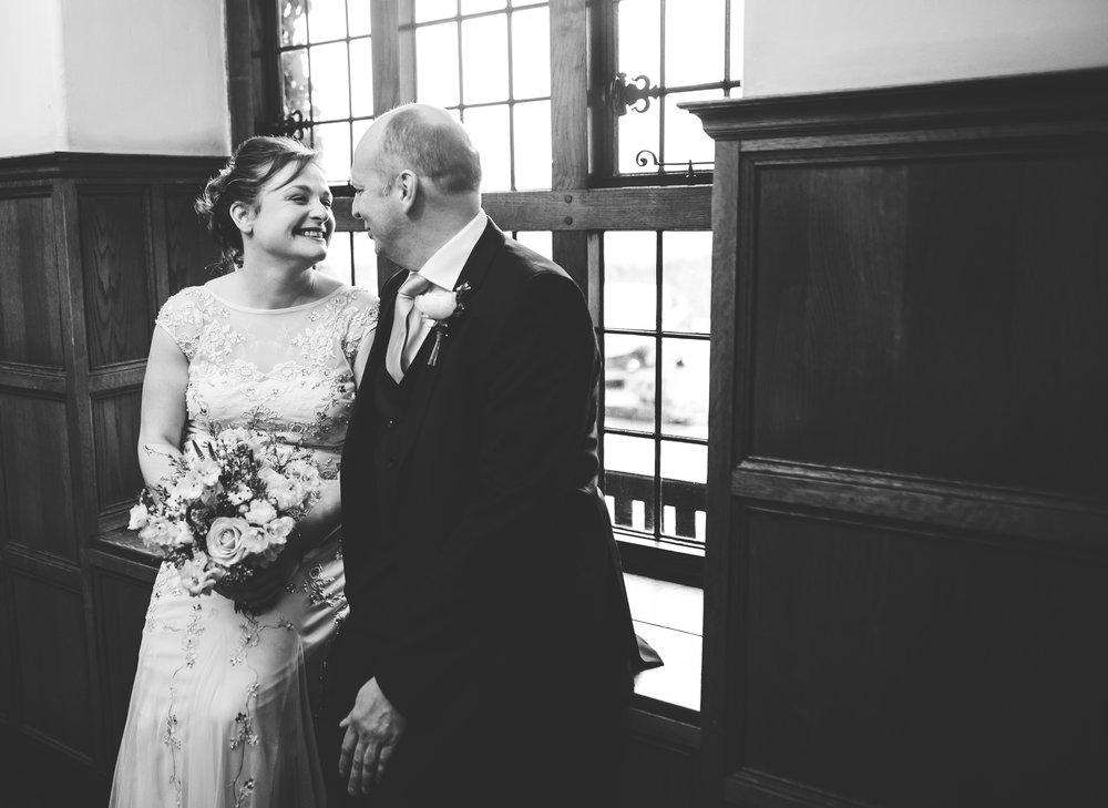 bride and groom laughing together - black and white wedding photographer