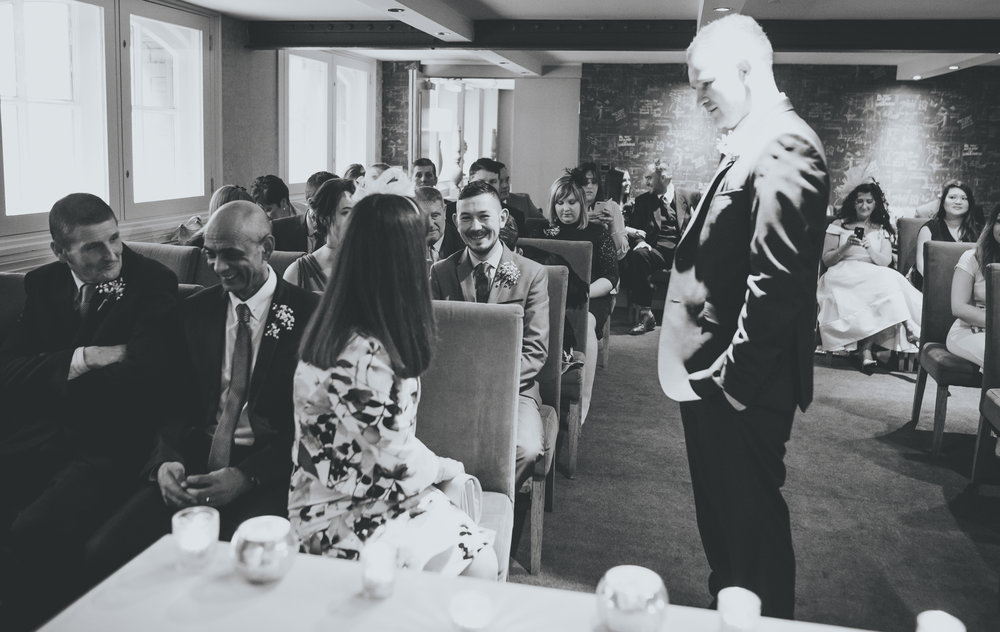 groom chats to guests before wedding ceremony