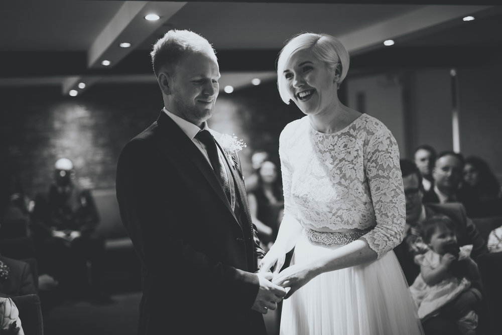bride and groom laugh during the wedding ceremony at great john street hotel manchester
