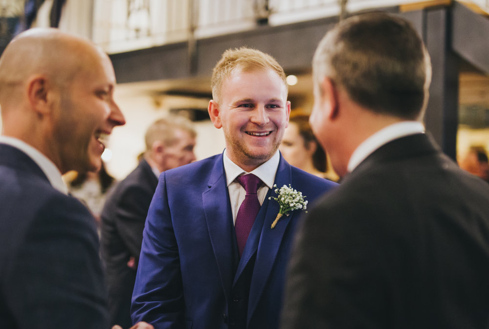 groom laughs with guests -documentary wedding photography