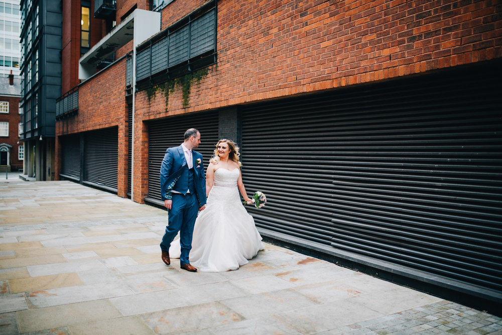 bride and groom walk hand in hand through Manchester City centre