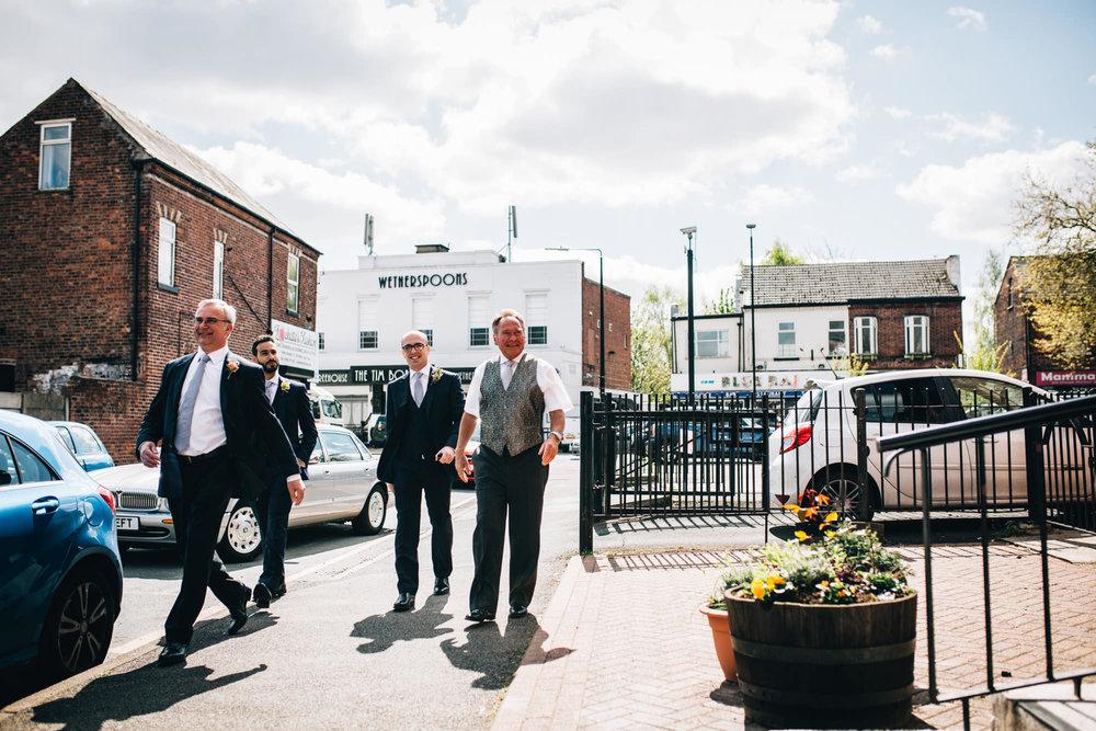 groom and groomsmen walk down the road to church - wedding photographer cheshire