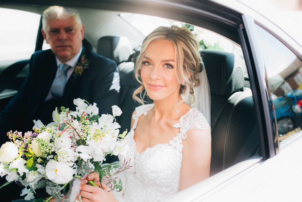 bride arrives at church smiling = wedding photographer cheshire
