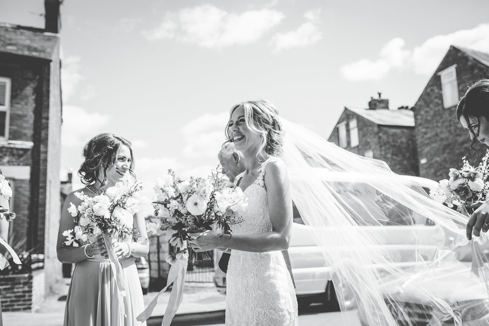 creative wedding photographer in cheshire - bride and bridal party arrive at church