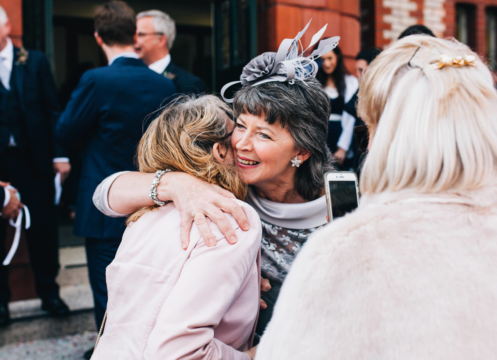 hugs and kisses outside church - wedding photographer cheshire