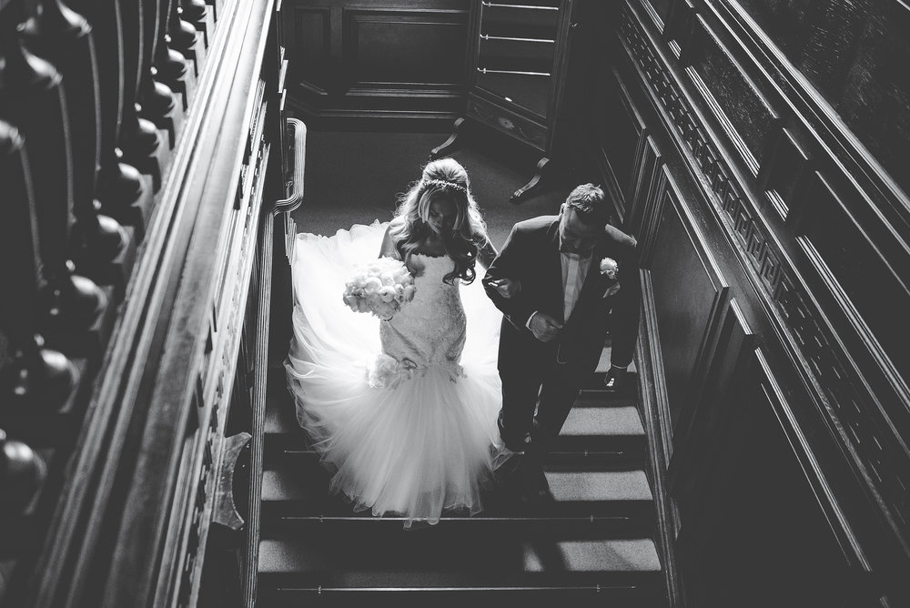 bride walks down the staircase at eaves hall