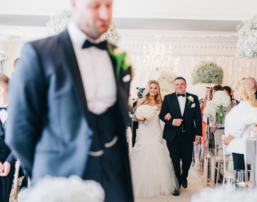bride and her dad walk down the aisle at Eaves Hall wedding