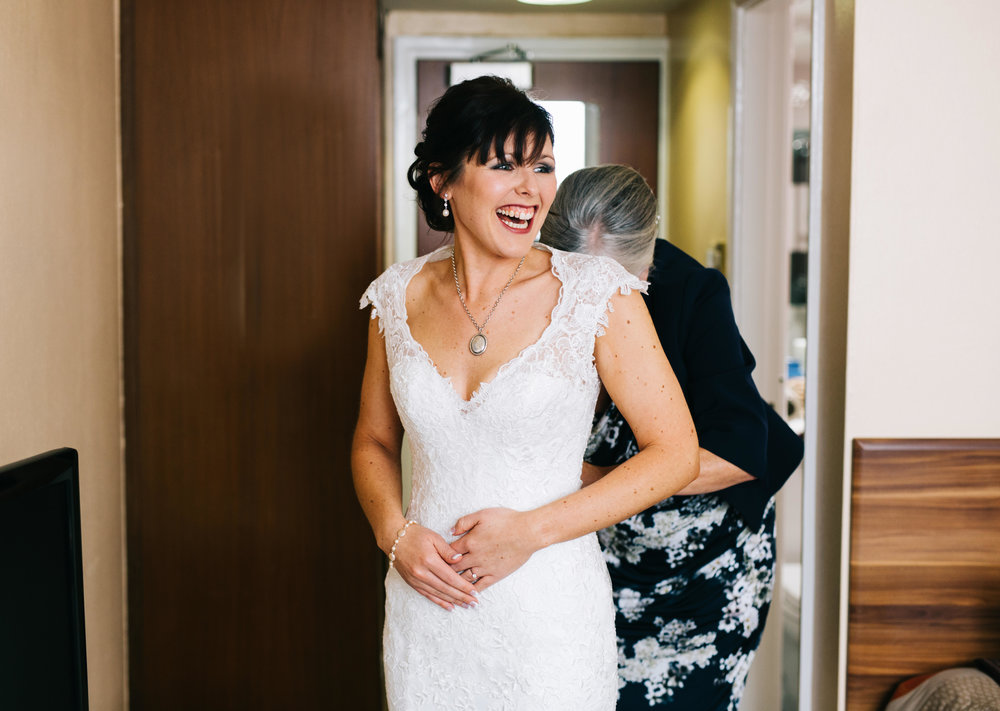 mum helps the bride get dressed - manchester wedding