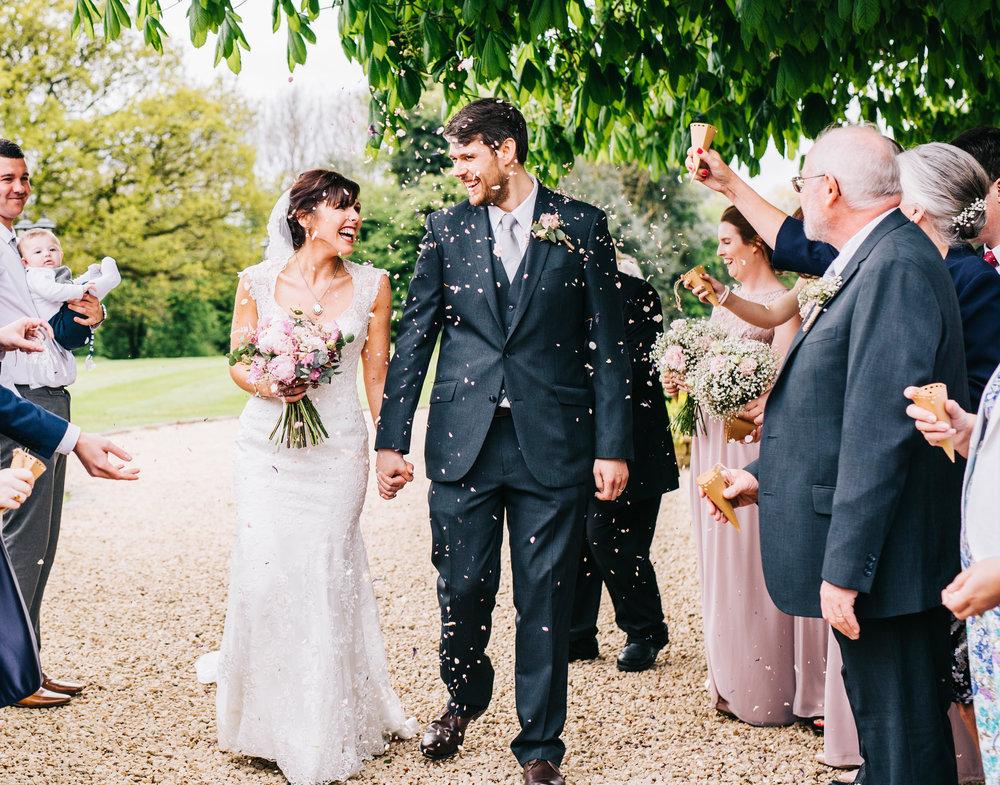 bride and groom walk through confetti in manchester wedding