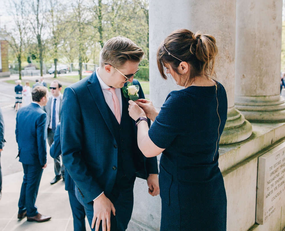 Rose getting place in button hole, Documentary wedding photography, Ashton memorial for a wedding.