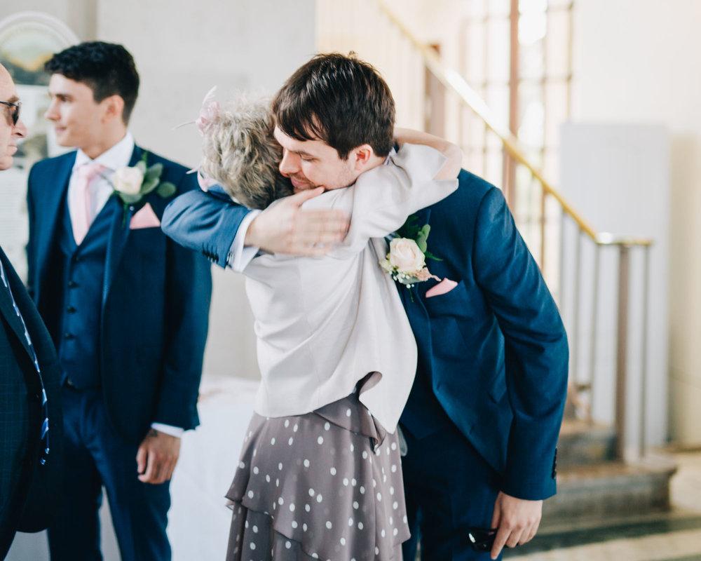 Groom hugging wedding guests, Ashton Memorial for a wedding, Documentary photographer.