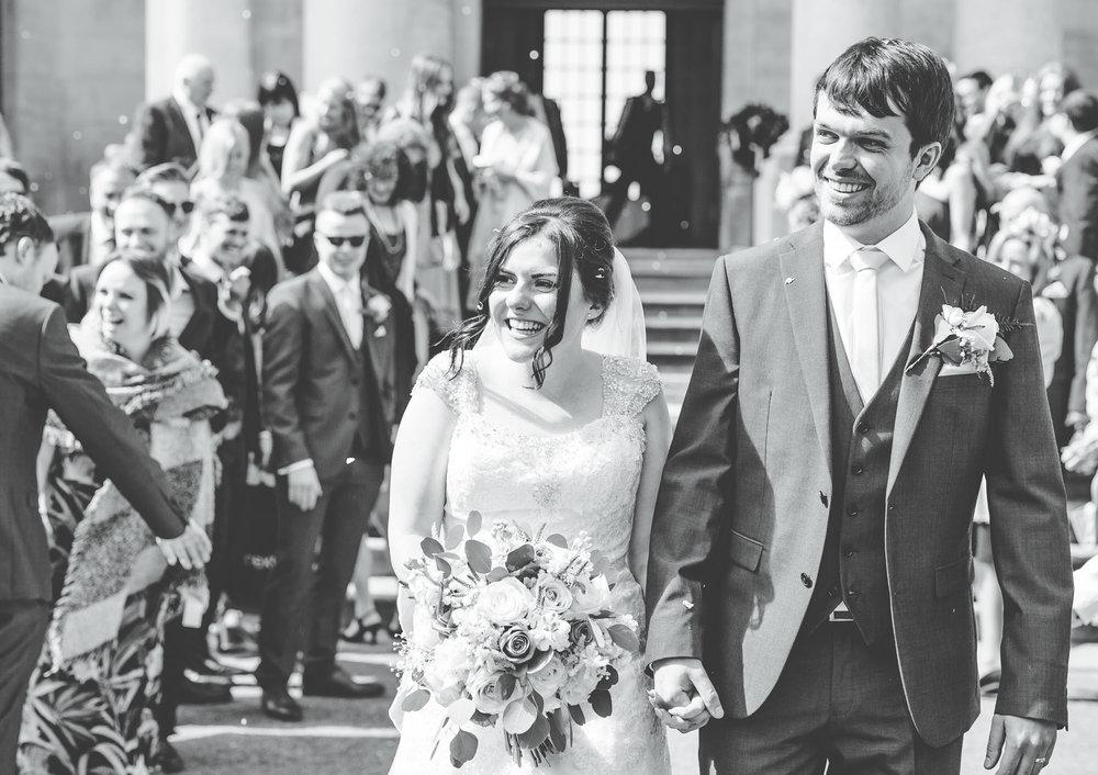 Black and white photo of the smiling bride and groom, Confetti walk, Ashton Memorial wedding, Documentary wedding photos.
